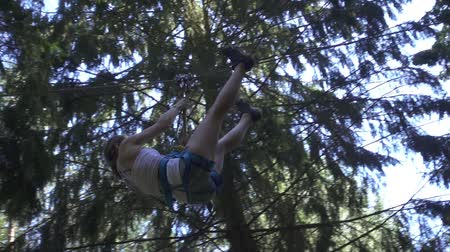 carabine : Young woman in safety equipment moving on rope with carbine on high in climbing park. Summer adventure climbing trees in extreme park outdoor Stock Footage