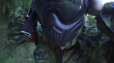 paintball : Young man putting paintball mask on head before shooting game. Close up paintball player putting protective mask for protective head and face in extreme games