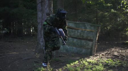 Man player in paintball game with gun running on shooting range slow motion. Paintball team attacking enemy on battle field during shooting game in forest Wideo