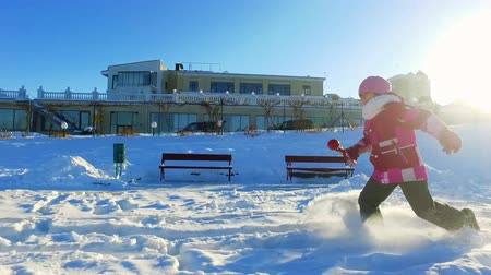 Side view of little girl running in winter park. Child having fun outdoors in slow motion. Young cheerful girl have fun on snow