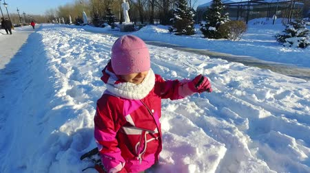 Little girl playing on snow in slow motion. Child having fun outdoors in winter. Carefree kid playing in snow. Happy wintertime Wideo