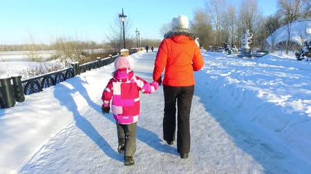 Back view mother and daughter running in winter park. Family fun on snow pathway. Daughter and mother walking in winter path in slow motion Wideo