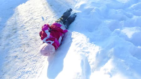 Little girl lying on snow. Child having fun on winter holidays. Carefree child playing in snow in slow motion. Winter kid have fun. Happy snow girl