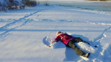 Child making snow angel in slow motion. Little girl having fun in snow. Winter kid holiday. Happy winter wonderland. Funny snow