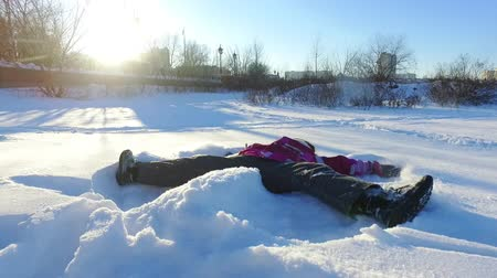 Little girl making snow angel in slow motion. Child having fun lying on snow. Winter holidays. Children fun on winter snow