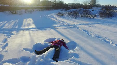 Little girl making snow angel. Child having fun outdoors in snow. Carefree child playing in snow. Happy winter children holiday