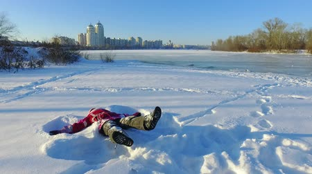 Happy little girl lying on snow in city park. Winter wonderland time. Fun snow angel in slow motion. Happy winter holiday. Snow playing