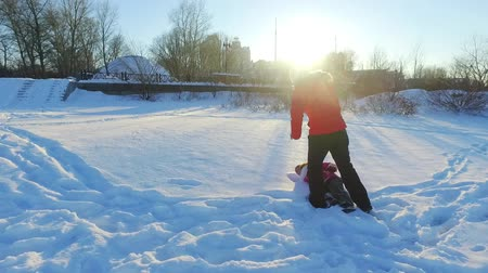Back view little girl playing with mother in snow. Mother and daughter have snow fun in slow motion. Winter family concept