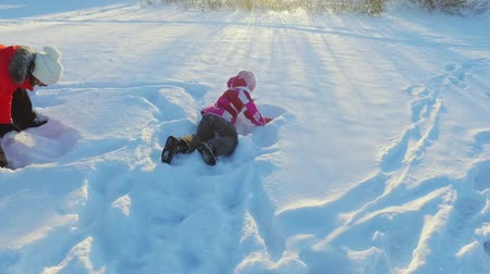 Mother playing snow with daughter in slow motion. Happy winter rest. Family have fun in sunny winter day Wideo