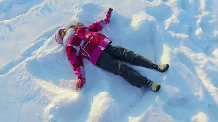 Top view little girl making snow angel. Child having fun on snow holiday. Carefree child playing in snow in slow motion. Winter christmas angel. Happy winter play