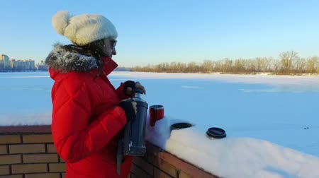 Young woman pouring tea in winter park. Woman with vacuum flask standing outdoors. Hot drink in thermo cup. Cozy winter relax Wideo
