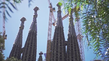 espana : Panoramic view of La Sagrada Familia cathedral in Barcelona city. Low angle view of old catholic church in modern European city. Barcelona city sightseeings. Historical building by Antonio Gaudi Stock Footage