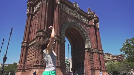 arco : Young woman turning around and smiling. Slow motion of cheerful and beautiful girl spinning around against Arc de Triomf. Woman tourist in barcelona city. Enjoy barcelona architecture Stock Footage
