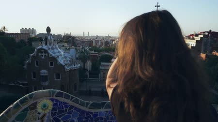 Back view of beautiful girl touching her hair. Young woman combing hair with hand and looking on modern Barcelona Gaudi park. Barcelona city sightseeings