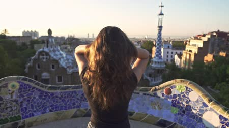 Young woman adjusting her hair while standing in Gaudi park. Beautiful girl touching hair with hand on Barcelona park at sunset. Enjoy Spain travel. Female back view near mosaic park buildings