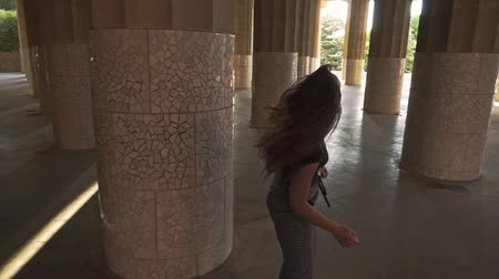 Steadyshot of beautiful girl turning around and smiling outdoors. Young woman walking and spinning around among columns of Park Guell building. Barcelona city sightseeings Wideo