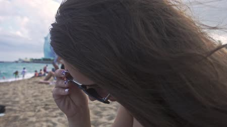 Woman with waving hair on wind. Portrait of beautiful girl wearing sunglasses on beach. Woman in sunglasses sitting at sandy plage. Female tourist face on beach