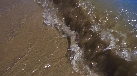 Sea waves on sandy beach. POV waves rolling in to beach. Point of view ocean splashes little waves. Sand ocean water background