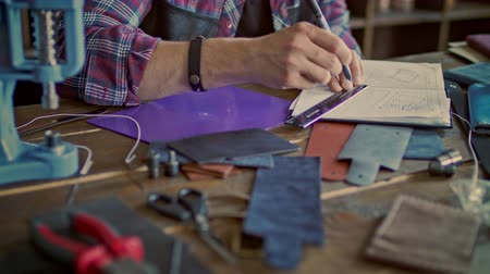 small pen : Leather maker drawing sketch of new product at leather workshop. Designer working on sketch in notebook. Close up of male hand draw sketch. Craftsman designing new leather product Stock Footage