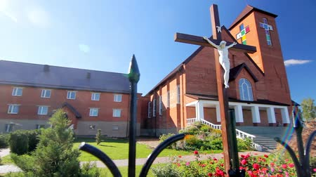crucifix : Jesus on cross in church yard. Religion and saint faith concepts. Exterior of modern catholic church. Religion building in sun weather Stock Footage