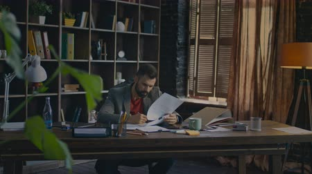 home studio : Serious business man reading documents at table. Young businessman signing documents at home office. Paperwork in creative studio. Business owner doing paper work Stock Footage