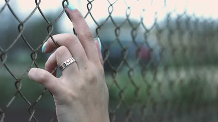 bükülme : Female hand with ring and blue manicure touching fence mesh walk on street. Close up woman hand touching fence mesh on street. Woman freedom concept Stok Video