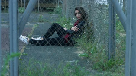 zmysłowy : Young woman sitting on ground and lean back at fence mesh on empty street. View through fence mesh sexy brunette sitting on ground. Sexy woman lifestyle model Wideo