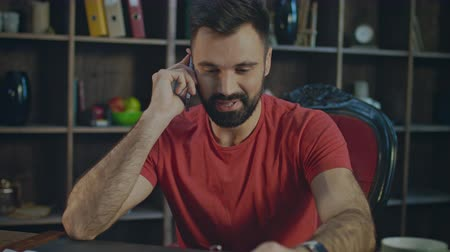 żart : Happy man talking mobile phone at home workplace. Smiling business man talking phone in cozy office. Portrait of happy man laugthing during phone talk at table