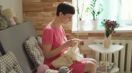 závit : Creative woman knitting wool sitting at couch in home. Talking woman knitting needles wool clothes in home workshop