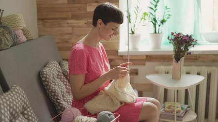 furnishing : Smiling woman knitting needles woolen clothes in cozy workshop. Happy woman sitting on couch and knitting wool yarn at home