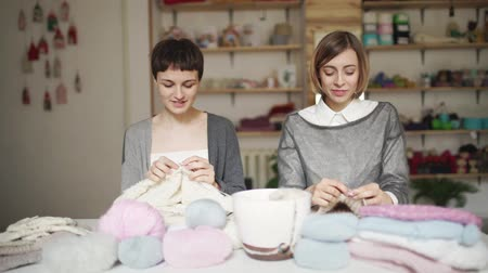 vyšívání : Two woman in knitted sweater smiling and enjoy hobby. Two woman friends together knitting wool clothes in workroom