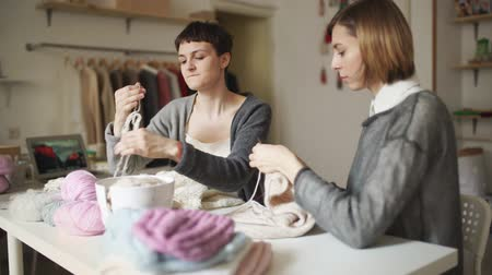 vyšívání : Two woman knitter working together in textile workshop. Knitting woman making wool clothes sitting at table in creative studio Dostupné videozáznamy