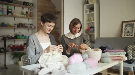 сплетни : Knitting woman working at table in sewing workshop. Two woman friends making wool fabric sitting at table in creative studio Стоковые видеозаписи