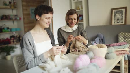 vyšívání : Two woman knitter working together in textile workshop. Woman knitter making wool fabric sitting at table in home sewing studio