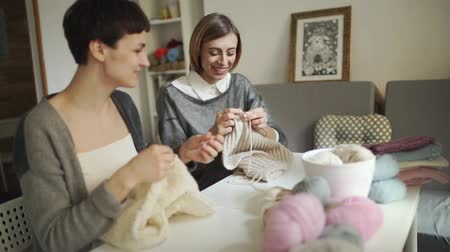 vyšívání : Two woman knitter talking and smiling in sewing studio. Two woman friends knitting woolen yarn in home studio. Fun girls making knitted fabric in workshop