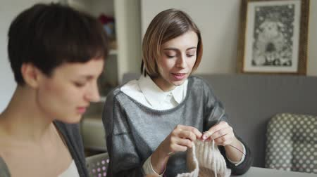 сплетни : Two young woman knitting wool yarn together in textile workshop. Two woman friends knitting needles in home studio