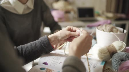 samples of fabric : Female hands knitting needles woolen yarn in home. Woman studying to knit clothes from wool yarn in workshop Stock Footage