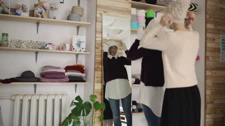 головной убор : Two woman friends fitting knitted hat in front mirror in show room. Young woman dressing together knitted cap and looking in mirror in small shop