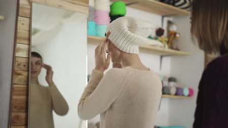 головной убор : Happy woman fitting knitted headdress in mirror at textile workshop. Smiling woman choosing knitted cap in retail shop. Customer in show room Стоковые видеозаписи