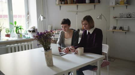 чат : Two woman students at table using notebook for online learning. Young woman looking on screen laptop in home. Women in cozy studio chatting online