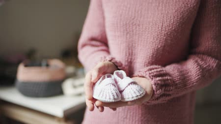 knitted : Baby booties on female palms. Close up knitted booties for newborn baby in mother hands. Knitted shoes handmade for children. Expecting mother in knitting wear Stock Footage