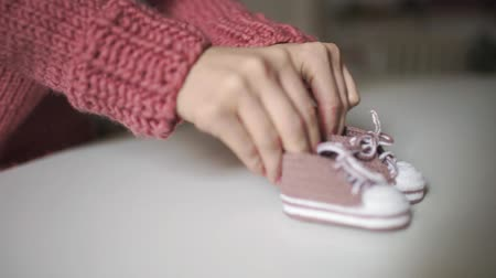 booties : Mother hands playing with knitted baby booties. Close up pink knitted booties for newborn in female hands. Knitted clothes for children. Expecting baby concept Stock Footage