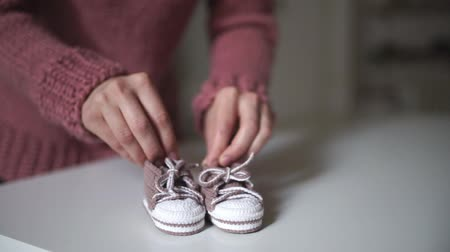 booties : Mother hands playing with pink baby booties. Close up knitted booties handmade for little girl in female hands. Knitted clothes for baby. Pregnancy concept. Happy expectant mother Stock Footage