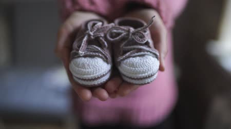 booties : Female hands showing baby booties. Close up handmade baby booties for newborn girl in mother hands. Knitted shoes for children. Pregnancy concept