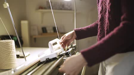 ladění : Creative woman preparing weaving machine for work at textile fabric. Woman hand tuning loom machine for making knitted fabric in textile workshop. Knitting machine in workshop