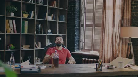 алкоголизм : Tired man drinking alcohol at workplace. Beard guy drinking scotch in office. Exhausted businessman pouring jack daniels whiskey in glass from bottle. Relax in office
