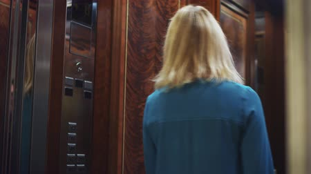 press wall : Opening mirror lift doors and young woman coming into elevator car. Close up woman entering into elevator car and door closing Stock Footage