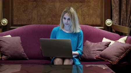 communion : Beautiful woman sitting on luxury sofa and working on notebook computer. Young woman using laptop during holiday in luxury room in hotel Stock Footage