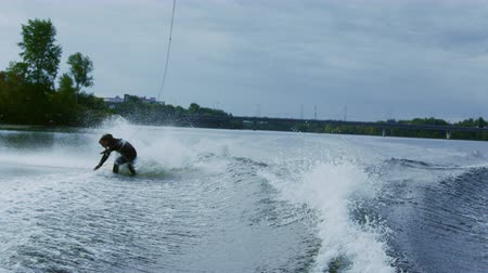 rider : Rider falling from wakeboard into river in slow motion. Sportsman failing. Fall on water. Water sports. Guy riding on waterski falling into water. Extreme lifestyle