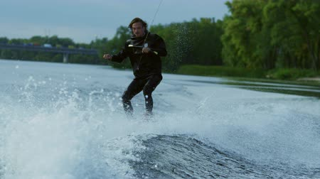 narciarz : Man riding wakeboard boat on river. Water rider enjoy waves. Extreme man wakeboarding boat. Virtuosity on wakeboard in slow motion. Extreme water sports. Extreme lifestyle